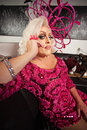 Blond drag queen sitting in pink dress on sofa Stock Images