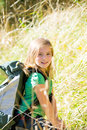Blond explorer kid girl walking with backpack in grass between forest Stock Image