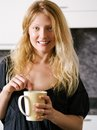 Blond female enjoying coffee at home photo of a beautiful holding a large Royalty Free Stock Image