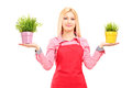 A blond female gardener holding two potted plants isolated on white background Royalty Free Stock Photography