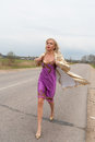 Blond female model in golden coat and purple dress walking on a countryside road Royalty Free Stock Photo