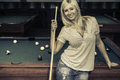 Blond female standing in front of a pool table in a pool house Stock Photography