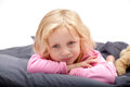 Blond girl beautiful small with green eyes in pink pyjamas lying on stomac Stock Photos