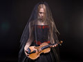 Blond girl with black veil holding fiddle Royalty Free Stock Photo