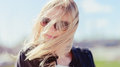 Blond girl closeup fashionable beautiful young wearing a leather jacket windy and warm sunny day Royalty Free Stock Photos