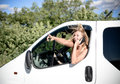 Blond girl driving car speaking on mobile phone picture of female and looking out of window young woman excited and smiling while Stock Photo
