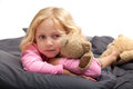 Blond girl with green eyes beautiful small in pink pyjamas lying on stomac hugging teddy bear Royalty Free Stock Images