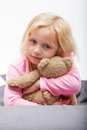Blond girl with green eyes beautiful small in pink pyjamas sitting and hugging teddy bear Stock Image