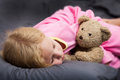 Blond girl with green eyes beautiful small in pink pyjamas sleeping teddy bear Stock Photo