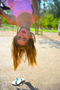 Blond girl hanging upside down in pink outfit Stock Photography