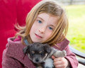 Blond girl hug a gray pyppy chihuahua dog puppy with winter coat Stock Photo