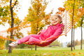 Blond girl laying on net of hammock in park Royalty Free Stock Photo