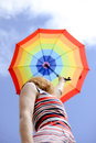 Blond girl looking up in blue sky under colorfull female umbrella at cloudy woman striped dress rising umbrella Royalty Free Stock Photography