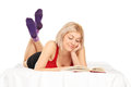 Blond girl lying on bed and reading a novel isolated white background Stock Photo