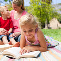 Blond girl reading while having a picnic Royalty Free Stock Photo