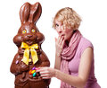 Blond girl stealing easter eggs of a chocolate bun bunny isolated on white background Royalty Free Stock Photos