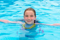Blond girl swimming in the pool with red cheeks kid sun tan Royalty Free Stock Photography
