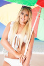 Blond girl under the sunshade portrait of a young in a white bikini standing a colorful at a beautiful beach with a turquoise sea Stock Photo