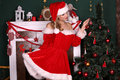 Blond girl wears Santa costume,posing beside Christmas tree and chimney Royalty Free Stock Photo