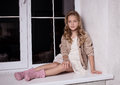 Blond girl on windowsill child model sitting Royalty Free Stock Image