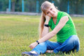 Blond girl young woman sitting on grass at summer green park Royalty Free Stock Photo