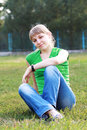 Blond girl young woman sitting on grass at summer green park Stock Photos