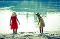 Blond girls in red dress and yellow dress at the river strand beautiful nymphs dancing by rear view Stock Photo