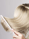 Blond hairpiece brushed by a woman Royalty Free Stock Photo