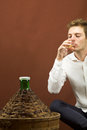 Blond handsome man drinking a glass of white wine near a carboy Royalty Free Stock Photo
