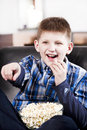 Blond happy boy watching tv and eating popcorn Stock Images