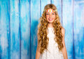 Blond happy hippie children girl smiling on blue wood grunge background Royalty Free Stock Image