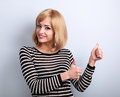 Blond happy smiling young woman showing thumb up sign by two han hands on blue background Stock Photo