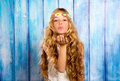 Blond hippie children girl blowing mouth with hand on blue grunge wood Stock Photos