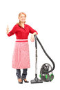 Blond housewife posing on a vacuum cleaner and giving thumb up Royalty Free Stock Image