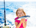 Blond kid girl fishing tuna little tunny happy with catch Royalty Free Stock Photo