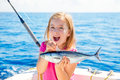 Blond kid girl fishing tuna little tunny happy with catch trolling on boat deck Royalty Free Stock Images