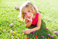 Blond kid girl lying relaxed in garden grass with flowers Royalty Free Stock Photo