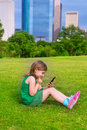 Blond kid girl playing with smartphone sitting on park lawn at c in city skyline background Stock Images