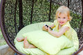 Blond kid girl playing with smartphone sitting in wicker chair