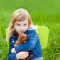 Blond kid girl with puppy pet dog in green grass Royalty Free Stock Photography