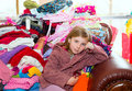 Blond kid girl sitting on a messy clothes sofa before folding laundry Stock Photo