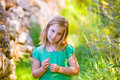 Blond kid girl smiling with purple flower relaxed outdoor in green Stock Photo