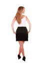 Blond lady looking right a beautiful in a black skirt is photographed from behind and she is over her shoulder the photo is Stock Images