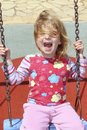 Blond little girl swinging park messy hair Stock Photos