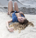 Blond long-haired girl lying on sand and looking at camera Royalty Free Stock Photo