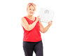 Blond mature female athlete holding a weight scale isolated on white background Royalty Free Stock Photos