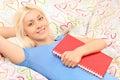 Blond meisje die in bed liggen en een notitieboekje houden Stock Afbeelding