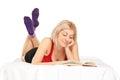 Blond meisje die op bed liggen en een roman lezen Stock Foto