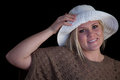 Blond model holding brim her white summer hat Stock Photography