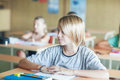 Blond schoolboy in the classroom cute sitting at his desk Royalty Free Stock Photo